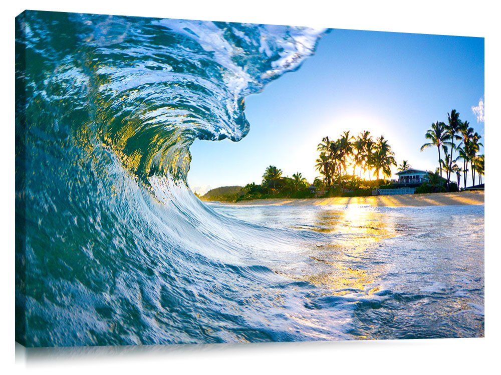An ocean wave breaking onto the beach during sunrise, on the north shore of Oahu.