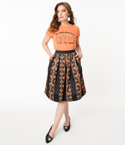 This is a Unique Vintage Halloween swing skirt that has black cats, bats and skulls with orange print and the model is wearing an orange shirt.