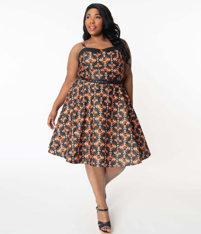 This is a Unique Vintage Halloween swing dress that has black cats, bats and skulls with orange print and the plus model is wearing black shoes.