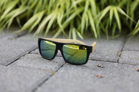 bamboo sun glasses with green lenses on paving stones