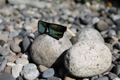 bamboo sun glasses with green lenses on stones