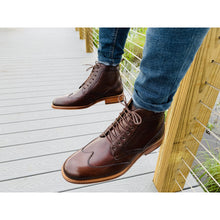 Dark brown leather boot with red hints, natural color sole, brogue design and wingtip