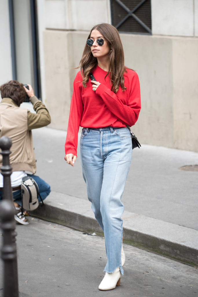 white boots and denim with red sweatshirt street style