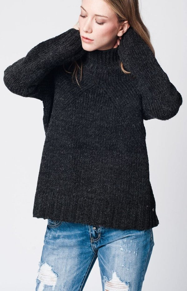 Woman wearing dark gray oversized knit sweater and jeans. Shop Women's Dark Gray Oversized Knit Sweater at Cultur'd Collective