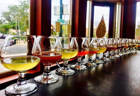 a variety of sour beers lined up on a long table
