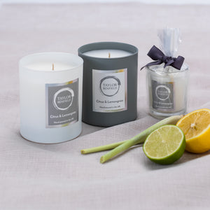 Taylor Benfield Citrus & Lemongrass luxury scented candles beautifully packaged in grey matte glass, white matte glass and a travel candle in clear glass with a grey ribbon, alongside limes, lemons and lemongrass.