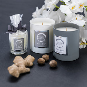 Taylor Benfield Floral & Ginger luxury scented candles beautifully packaged in grey matte glass, white matte glass and a travel candle in clear glass with a grey ribbon, alongside nutmeg, ginger and a gorgeous white orchid.