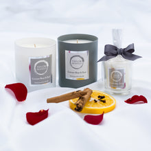 Taylor Benfield Crimson Rose & Oud luxury scented candles beautifully packaged in grey matte glass, white matte glass and a travel candle in clear glass with a grey ribbon, alongside cinnamon sticks, cloves, orange and rose petals.