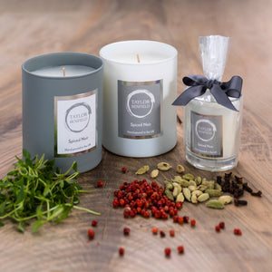 Taylor Benfield Spiced Noir scented candles beautifully packaged in grey matte glass, white matte glass and a travel candle in clear glass with a grey ribbon, alongside thyme, cloves, red pepper and cardamom.