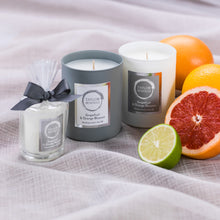 Taylor Benfield Grapefruit & Orange Blossom scented candles beautifully packaged in grey matte glass, white matte glass and a travel candle in clear glass with a grey ribbon, alongside limes, oranges and zesty red grapefruit.