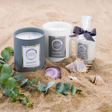 Taylor Benfield Summer Haze scented candles beautifully packaged in grey matte glass, white matte glass and a travel candle in clear glass with a grey ribbon, on a bed of Cornish sand with shells and eucalyptus.