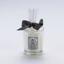 Taylor Benfield Crimson Rose & Oud luxury scented travel candle beautifully packaged in clear glass, wrapped with a grey ribbon.