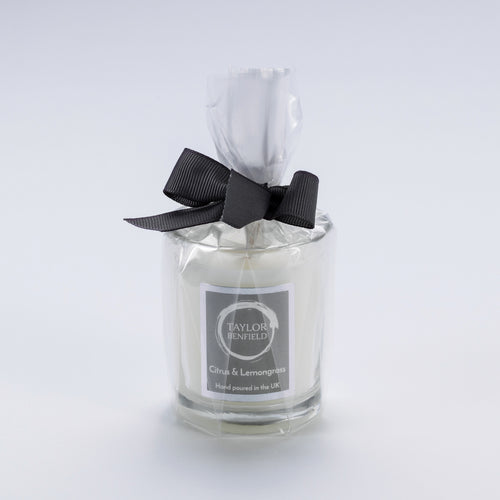 Taylor Benfield Citrus & Lemongrass luxury scented travel candle beautifully packaged in clear glass, wrapped with a grey ribbon.