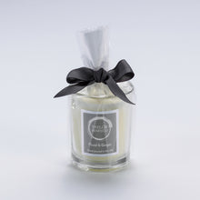 Taylor Benfield Floral & Ginger luxury scented travel candle beautifully packaged in clear glass, wrapped with a grey ribbon.