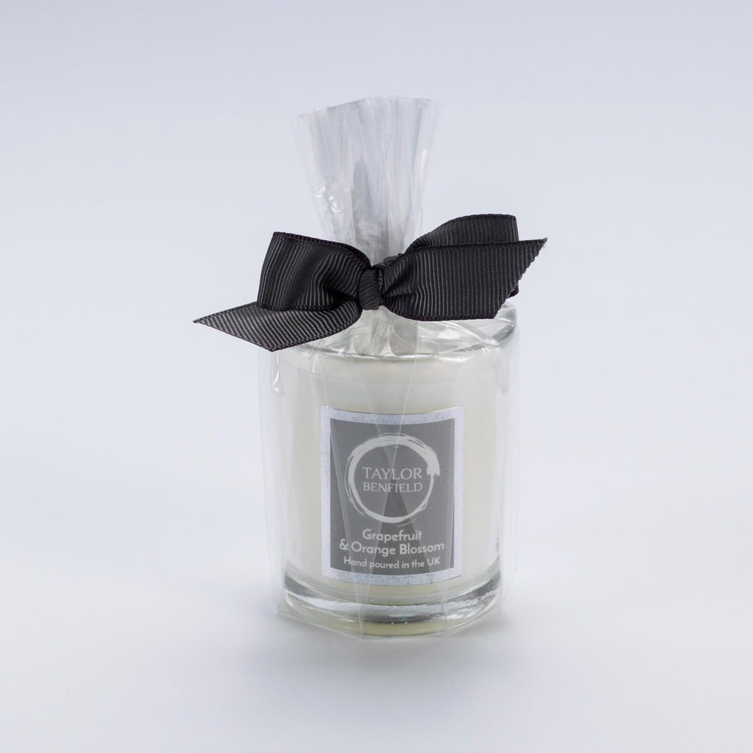Taylor Benfield Grapefruit & Orange Blossom luxury scented travel candle beautifully packaged in clear glass, wrapped with a grey ribbon.