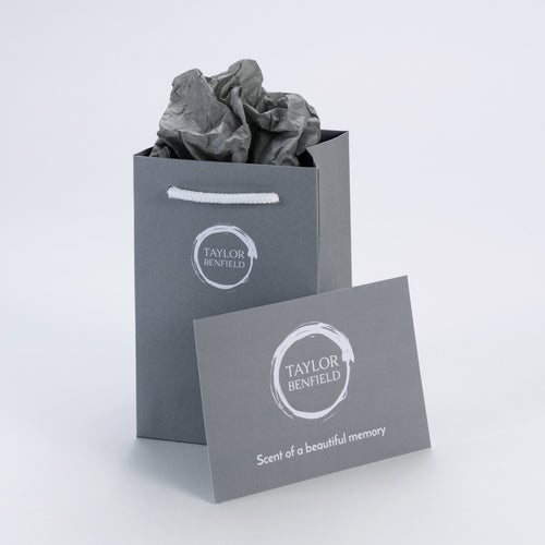 A grey branded gift bag, with grey tissue paper, and a Taylor Benfield card to be personalised.