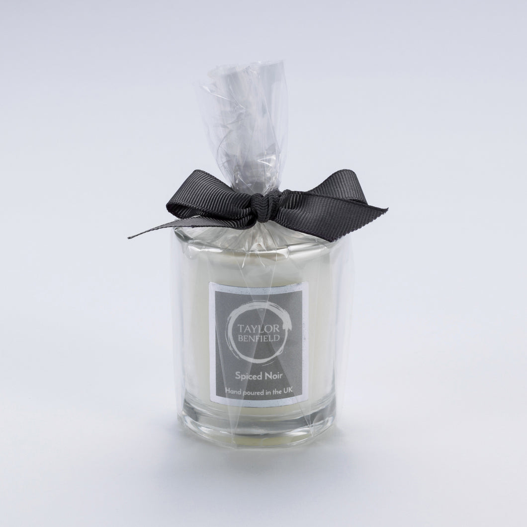 Taylor Benfield Spiced Noir luxury scented travel candle beautifully packaged in clear glass, wrapped with a grey ribbon.