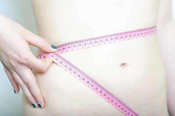 measuring waistline with measuring tape