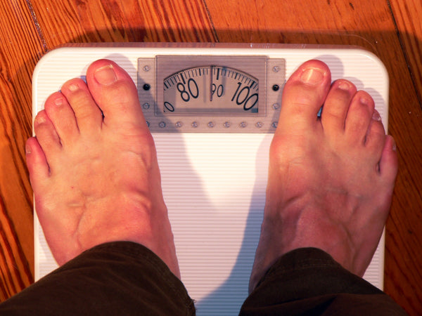 a pair of feet standing on a weighing scale