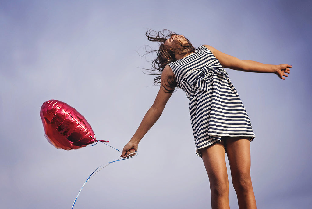 lady jumping for joy with balloon