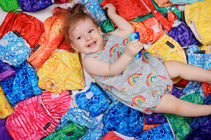 Happy baby playing in a pile of brightly coloured cloth nappies, wet bags, change mats and covers. Cloth nappy sea of colour. Blue, red, yellow, green, purple, orange and pink.