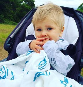 Toddler using Tiny Chipmunk 100% bamboo muslin swaddle blanket in buggy