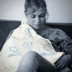 Mum breastfeeding using Tiny Chipmunk muslin swaddle blanket as cover