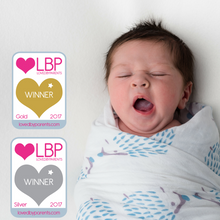 Baby wrapped in Tiny Chipmunk bamboo muslin swaddle blanket with award logos