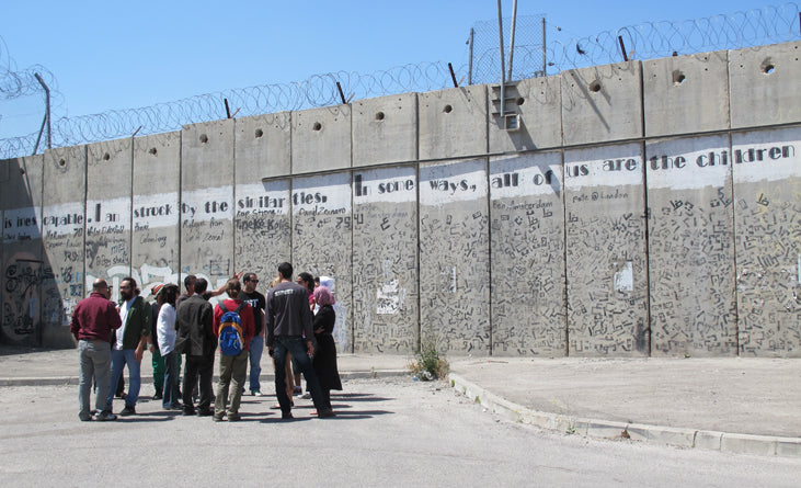 Roadtrip with the Palestinian graffiti community (10 people!). Here we are standing by the big wall Israel build.