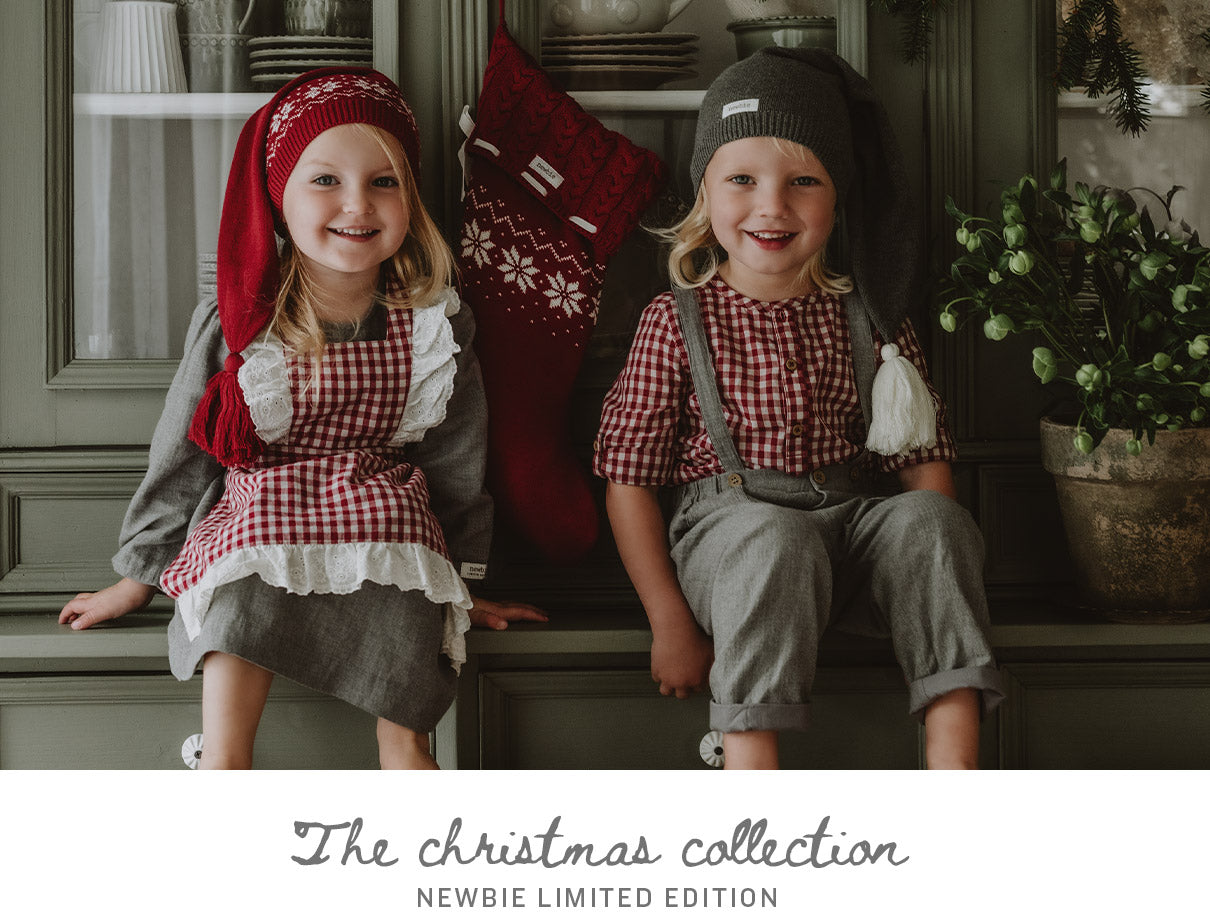 Two children sitting on ledge wearing Newbie Limited Edition Christmas Collection