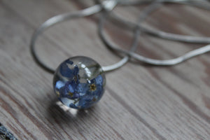 Blue flowers in a glass necklace