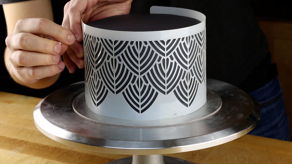 Wrap the stencil around the cake using pins to hold it in position