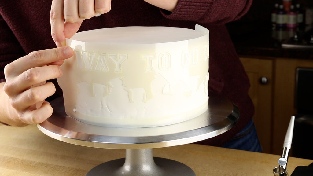 Fasten the stencil to the side of the cake using sewing pins