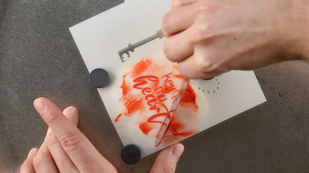 Smoothly scrape the royal icing through the cookie stencil