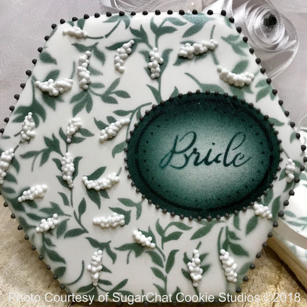 Beautifully stenciled cookie made our wedding cookie stencil or Bridal shower stencil. A flowered background with a framed text Bride dark on a light background