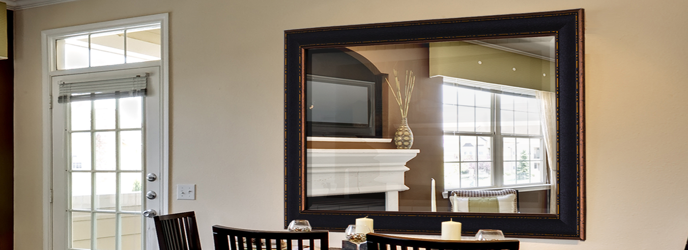 Black and gold mirror hanging on wall in dining room