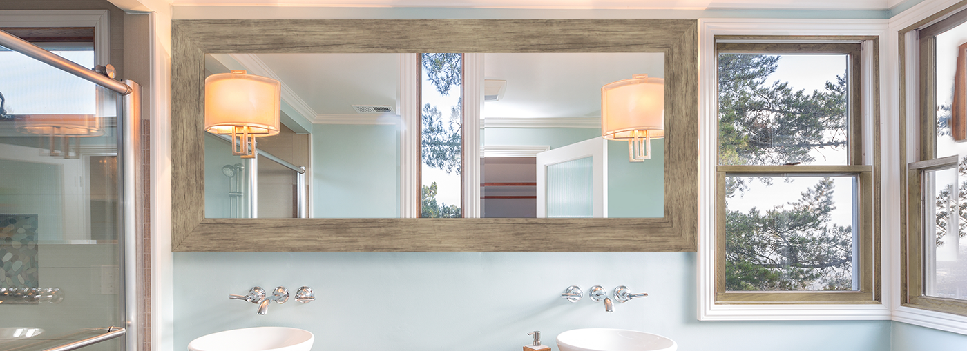 Distressed brown barnwood mirror hanging over bathroom vanity