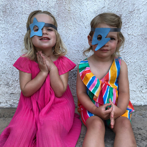 Two girls wearing blue Doudoods star + flash dress up eye patches