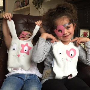 Two toddler girls playing with The Doudoods white + pink heart + star style baby comforters and matching dress up eye patches