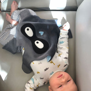 Baby boy lying with The DouDoods grey + black bandit style baby comforter on tummy