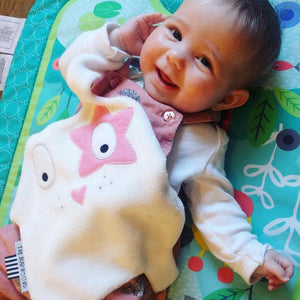 The Doudoods white + pink star style baby comforter being played with by baby girl