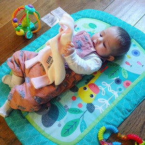 Baby girl playing with The Doudoods white + pink star style baby comforter