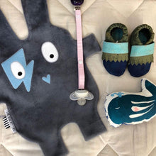 Composition of The Doudoods grey + blue flash style baby comforter, dummy clip, baby booties and whale rattle