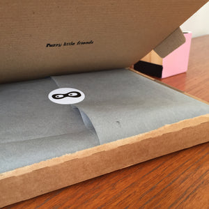 Postal box opening revealing tissue paper and The Doudoods brand sticker
