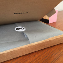 Open postal box showing grey tissue and brand sticker