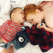 Brothers playing on bed with The DouDoods grey + black bandit style baby comforter