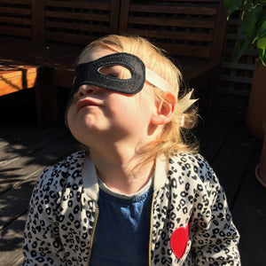 Smiling baby in The Doudoods black superhero dress up mask bandit style