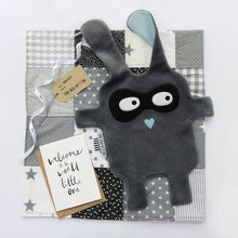 The DouDoods grey + black bandit style baby comforter on patchwork blanket and welcome to the world card