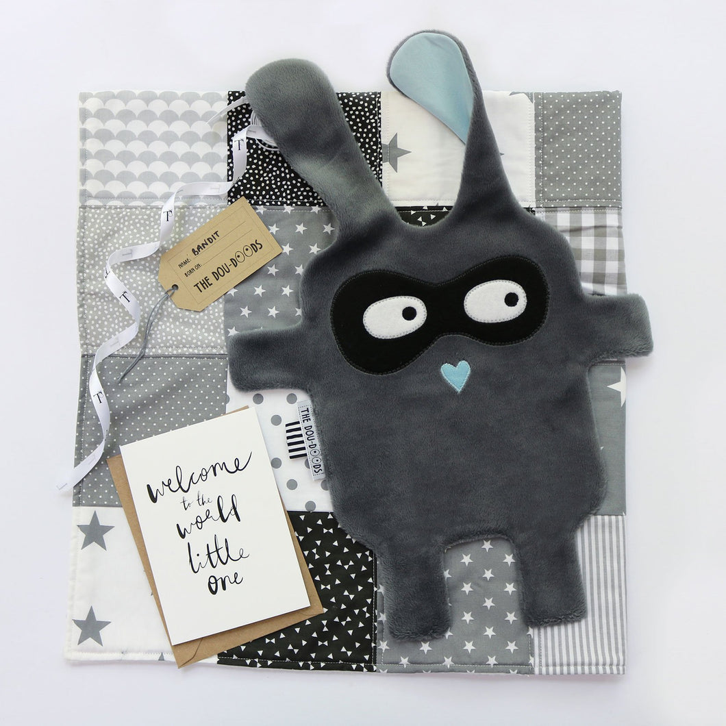 Grey + black Doudoods bandit baby comforter on patchwork blanket and welcome to the world card