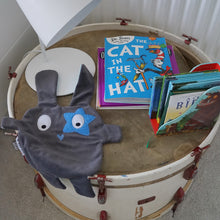 The Doudoods grey + blue star style baby comforter on drum with books